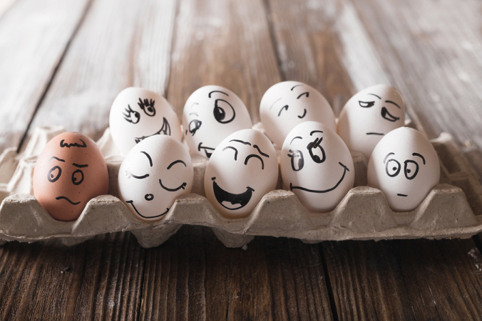 Eggs with funny faces in an open egg carton on wood floor