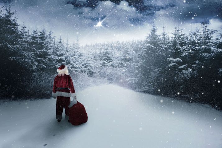 Santa carrying sack of gifts  against snow scene