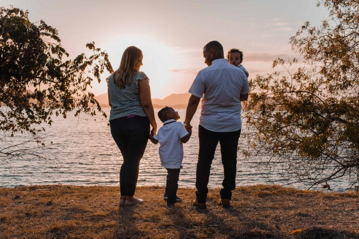 two parents standing holding the hand of a child between them and Dad holding the other child facing a body of water while the sun is setting